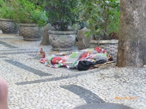 The uneven sidewalks in front of the hotel, along with a sleep homeless Brazilian.